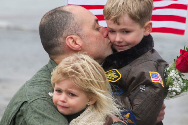 US Navy Aviator hugs his kids during the squadron's homecoming